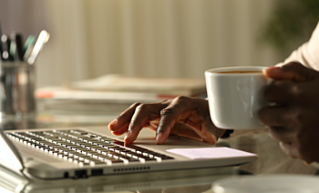 typing on computer with coffee