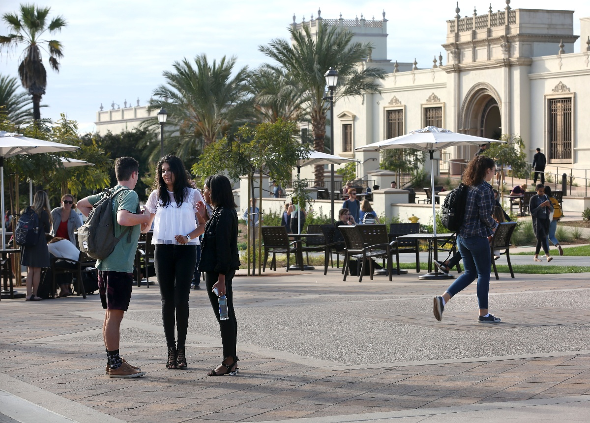 group-of-three-students-talk-on-university-of-san-diego-campus